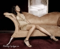 Glamorous Ashanti sitting on the brown couch