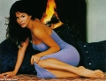 Brooke Burke posing next to fireplace