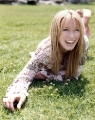 Hilary Duff smiling while laying on the grass