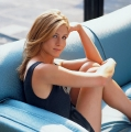 Jennifer Aniston posing on the blue couch showing great legs