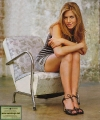 Jennifer Aniston in short dress posing on the chair