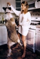 Jennifer Aniston is feeding her dog in the kitchen