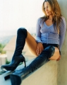 Jennifer Lopez posing in trasparent blouse and leather boots