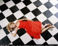 Nicole Richie posing in sexy red dress on the chequered froor