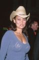 Tia Carrere in cowboy hat exposing naked neckline