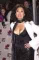 Tia Carrere wearing black dress with plunging neckline