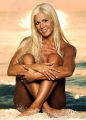 Torrie Wilson sitting nude on the beach