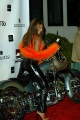 Traci Bingham posing on Harley wearing hot leather pants