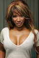 Traci Bingham wearing gray dress with hot neckline